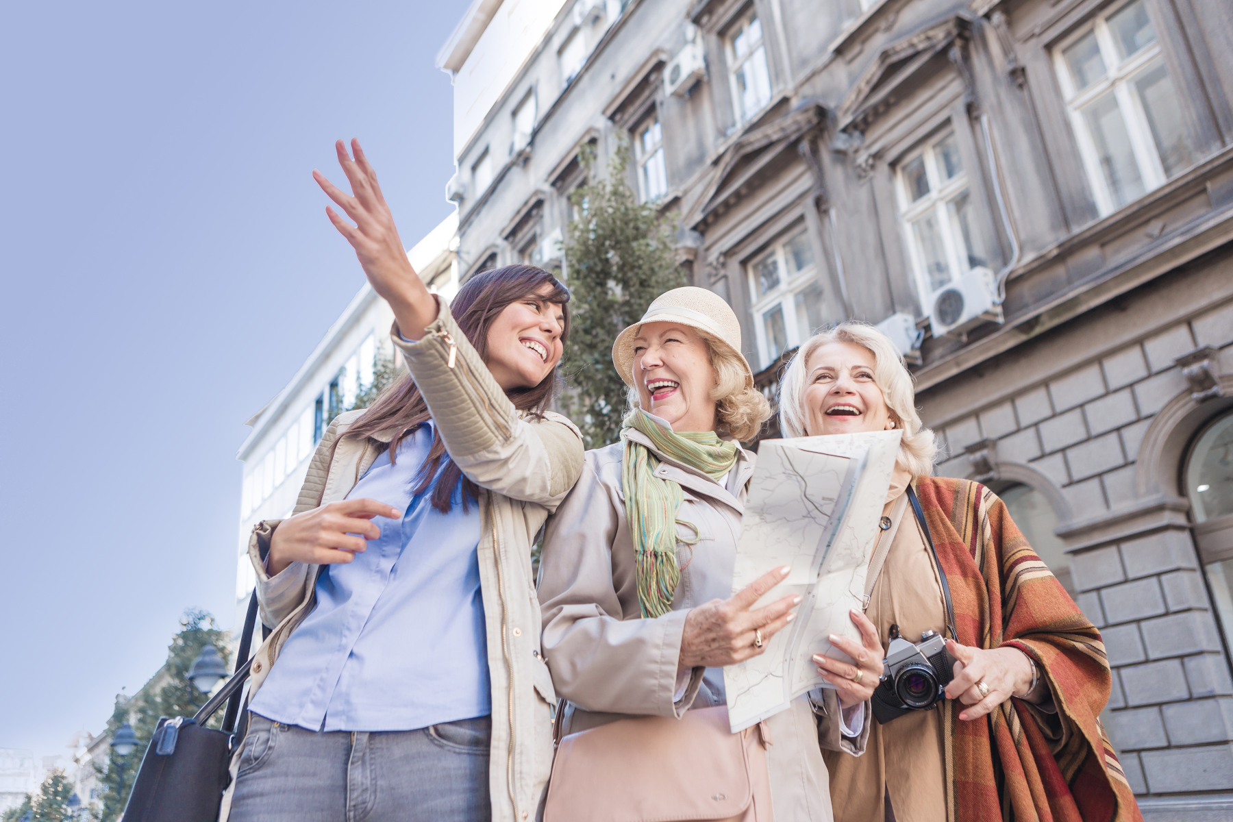 Two senior ladies, tourist traveling, exploring the city, asking young woman, passenger for directions, browsing city map, discovering landmarks.